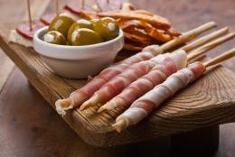 oliver i skål och spansk skinka lindad kring brödpinnar serverad på ett litet bord av trä