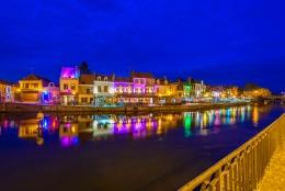 Hus i Amiens upplysta i olika neonfärger på kvällen vid floden