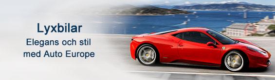 En exklusiv, röd sportbil som kör längs med en kuststräcka